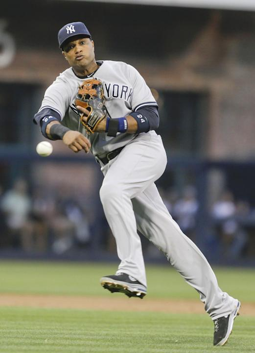 New York Yankees second baseman Robinson Cano makes the difficult throw for the out at first after fielding a deflected grounder by San Diego Padres' Jedd Gyorko in the first inning of an interlea