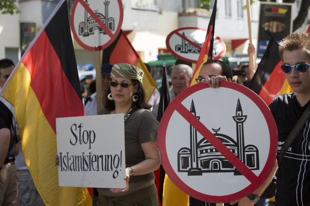 Demonstrators display signs with crossed mosques during a protest in front of a mosque in Berlin, Germany, Saturday, Aug. 18, 2012. A Berlin court had allowed the demonstration of the far-right group &#39; Pro Deutschland&#39; held under the slogan &quot;Islam does not belong in Germany  stop Islamization.&quot; (AP Photo/Gero Breloer)