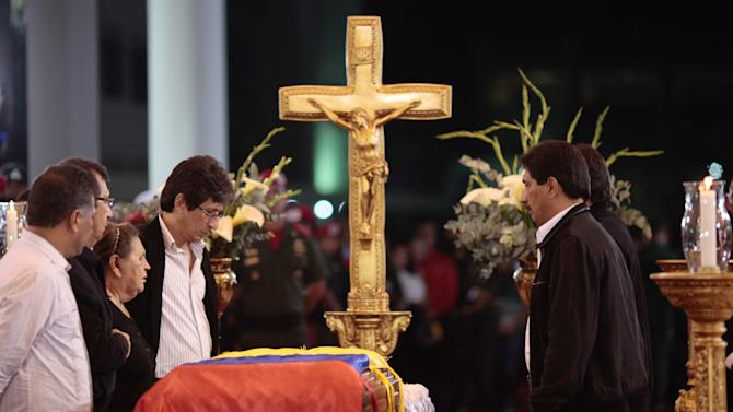 In this photo released by Miraflores Press Office,  Hugo Chavez' mother Elena Frias, third from left, and brothers Adan, second from left, Argenis, first right, and Adelis, fourth from right, stand next to the flag-draped coffin containing the body of Venezuela's late President Hugo Chavez on display during his wake at a military academy where his body will lie in state until his funeral in in state in Caracas, Venezuela, Wednesday, March 6, 2013. Seven days of mourning were declared, all schools were suspended for the week and friendly heads of state were expected for an elaborate funeral Friday. (AP Photo/Miraflores Presidential Press Office)