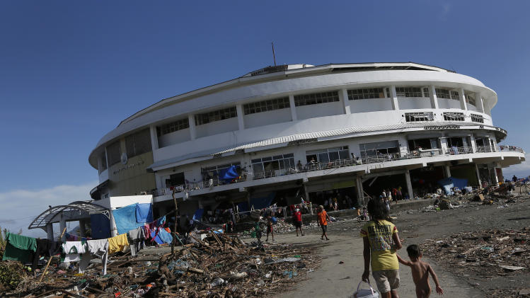 A young girl walks her brother to the Tacloban City Convention Center known as the Astrodome Thursday, Nov. 14, 2013, where hundreds of displaced typhoon survivors have set up makeshift shelters throughout the complex's once bustling shops and popular basketball court. For the thousands of people jamming the Tacloban City Astrodome, the great halls with a solid roof was a heaven-sent refuge when Typhoon Haiyan rammed eastern Philippines on Friday. Evacuated from their homes along the coast in time, they had a place to hide from the furious winds and gigantic water surge. But along with shelter, their constant companion now is misery and hunger. (AP Photo/Vincent Yu)