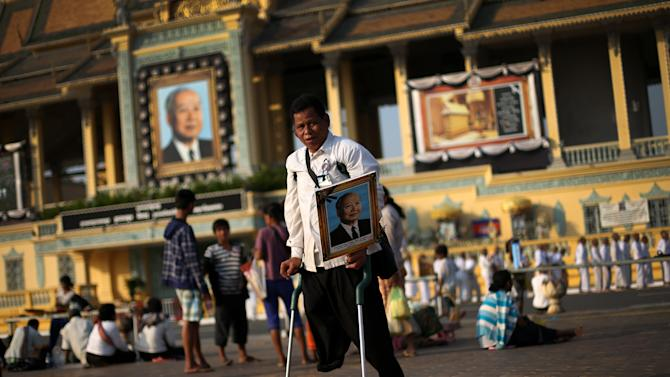 A mourner carries a portrait of the late former Cambodian King Norodom Sihanouk in Phnom Penh, Saturday, Feb. 2, 2013. Sihanouk's body had been lying in state at the Royal Palace after being flown from Beijing where he died Oct. 15 of a heart attack at the age of 89. The cremation, the climax of seven days of mourning, will take place Monday.(AP Photo/Wong Maye-E)