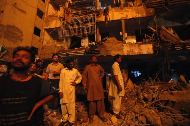 Residents stand in front of a damaged building after a bomb blast in a residential area in Karachi