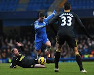 Chelsea midfielder Eden Hazard (C) jumps a sliding tackle from Wigan Athletic defender Ronnie Stam at Stamford Bridge, on February 9, 2013. Chelsea won 4-1 to ease some of the pressure on interim manager Rafael Benitez