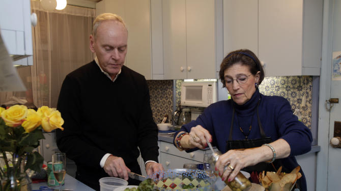 """Karen Nelson, and her house guest Gregory Downer prepare dinner in her upper west side apartment, in New York, Thursday evening, Nov. 1, 2012. Like herself, her neighbors have taken in dozens of """"refugees,"""" people who have fled their cold, dark homes in search of a roof, food, a hot shower and juice for their cell phones, iPads and laptops. (AP Photo/Richard Drew)"""