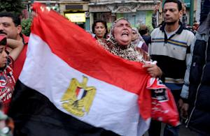 An Egyptian woman holds the national flag during …