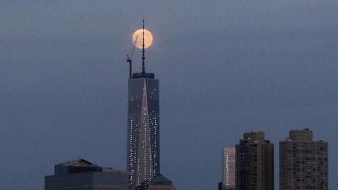 The moon is seen in its waxing gibbous stage as it rises over Lower Manhattan, including One World Trade Center, center, seen from The Heights neighborhood of Jersey City, N.J., Saturday, June 22, 2013. The moon, which will reach its full stage on Sunday, is expected to be seen 13.5 percent larger than usual during a phenomenon known as supermoon. (AP Photo/Julio Cortez)