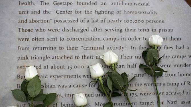 Flowers are placed on a monument honoring gays and lesbians persecuted by the Nazis during World War II for their sexual orientation and gender identity, In Tel Aviv, Israel, Friday, Jan. 10, 2014. The landmark joins similar memorials in Berlin, Amsterdam, Sydney and San Francisco dedicated to gay victims of the Holocaust. While Israel has scores of monuments for the genocide, the Tel Aviv memorial is the first that deals universally with Jewish and non-Jewish victims alike. (AP Photo/Oded Balilty)