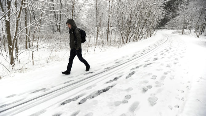 Penn State student Andrew Huffard walks along the bicycle path near Sunset Park, in State College, Pa., on his way to campus, Monday, March 25, 2013. Heavy snow fell throughout Centre County, Monday, causing local schools to be closed and hazardous traveling conditions.  (AP Photo/Centre Daily Times, Nabil K. Mark) MANDATORY CREDIT; MAGS OUT