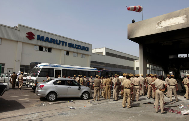 Policemen stand inside the Maruti Suzuki factory a day after workers rioted in Manesar, near New Delhi, India, Thursday, July 19, 2012. Top Indian carmaker Maruti Suzuki has shut one of its two factor