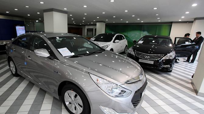 Customers look at Hyundai Motor Co.'s Grandeur at the South Korean automaker's showroom in Seoul, South Korea, Thursday, Jan. 24, 2013.   South Korea's Hyundai Motor Co. reported its lowest quarterly profit in nearly two years due to a surge in the local currency and lackluster car sales at home.(AP Photo/Ahn Young-joon)