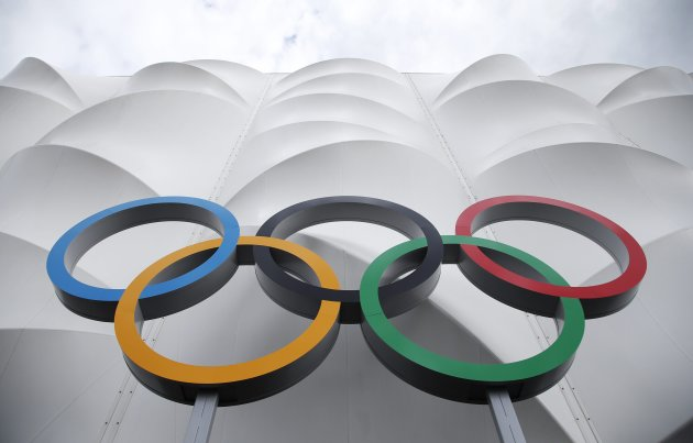 FILE - This July 15, 2012 file photo shows the Olympic rings displayed outside the basketball arena in the Olympic Park before the start of the 2012 Summer Olympics in London. The Summer Olympics opening ceremony takes place Friday, but the first of 5,535 hours that NBC is showing of the games begins Wednesday with qualifying rounds in women's soccer. With so many different options, viewers need a road map to make sense of it all. NBC is promising that every competition in London will be available to U.S. consumers live, with the bulk of them seen online. (AP Photo/Jae Hong, file)