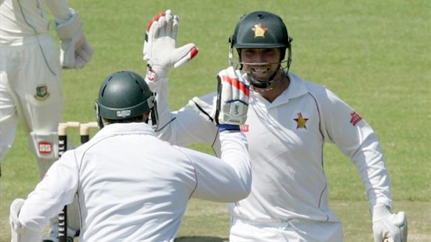 Zimbabwe captain Brendan Taylor (R) celebrates his 2nd century with team-mate Keegan Meth (L) during the fourth day of the first Test match between Zimbabwe and Bangladesh (AFP)