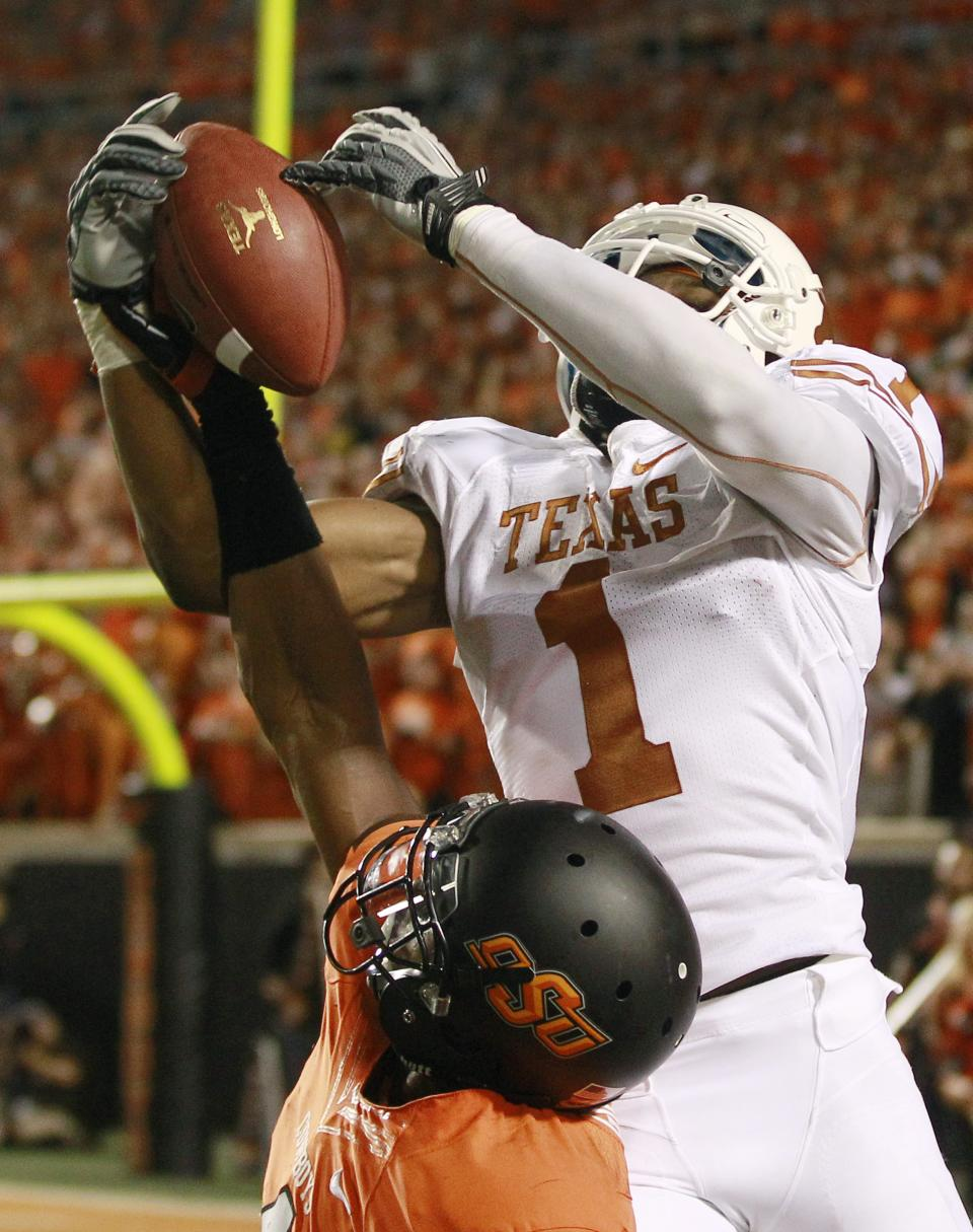 Texas wide receiver Mike Davis (1) catches a pass overOklahoma State cornerback Justin Gilbert (4) during the fourth quarter of an NCAA college football game in Stillwater, Okla., Saturday, Sept. 29, 2012. Texas won 41-36. (AP Photo/Sue Ogrocki)