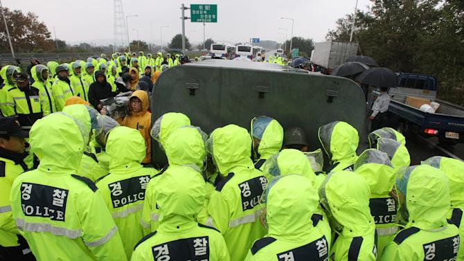 Police officers block a truck containing anti-North Korea leaflets on a road in Paju near demilitarized zone, South Korea, Monday, Oct. 22, 2012. South Korea has banned activists from launching propaganda leaflets to North Korea after North Korea threatened to attack.(AP Photo/Ahn Young-joon)