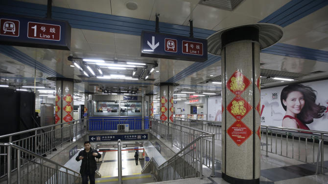 A passenger walks out of a station of the Subway Line Number 1 on the eve of the Chinese Lunar New Year in Beijing