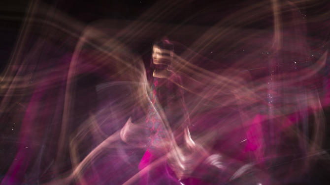 In this photo made with a long exposure, a model walks the runway at the Anna Sui Fall 2013 fashion show during Fashion Week, Wednesday, Feb. 13, 2013, in New York. (AP Photo/John Minchillo)