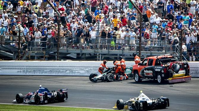 THM24. Indianapolis (United States), 24/05/2015.- Cars driven by Jack Hawksworth of Great Britain (L) and Josef Newgarden of the US (R) drive past track safety crew members as they assist Ed Carpenter of the US after he crashed into the turn one wall during the 99th running of the Indianapolis 500 auto race at the Indianapolis Motor Speedway in Indianapolis, Indiana, USA, 24 May 2015. (Estados Unidos) EFE/EPA/TANNEN MAURY