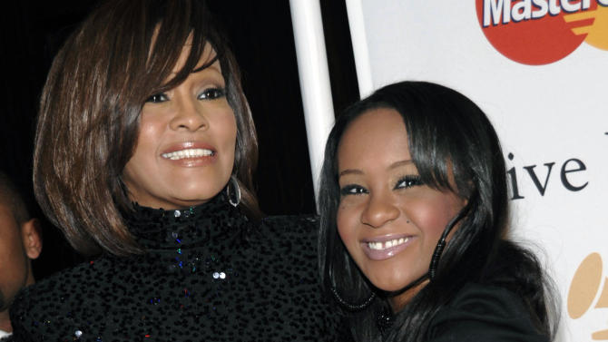 FILE - In this Feb. 12, 2011, file photo, singer Whitney Houston, left, and daughter Bobbi Kristina Brown arrive at an event in Beverly Hills, Calif. Brown, who was in hospice after months of receiving medical care, died on Sunday, July 26, 2015. (AP Photo/Dan Steinberg, File)
