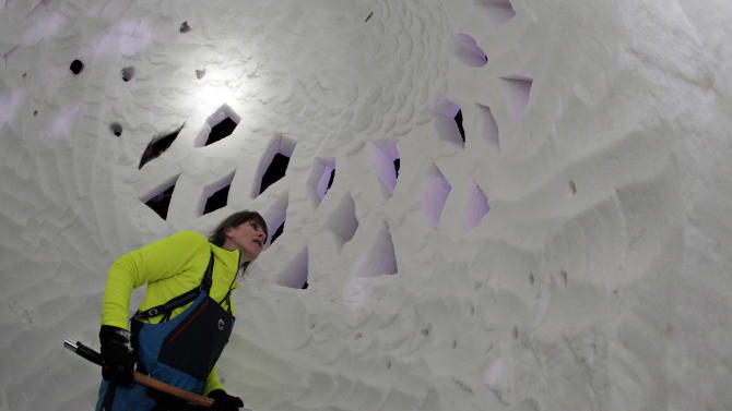 Sara Jonsdottir of Team Iceland stands inside of her snow sculpture called Lopapeysa, as she works late into the night at the 23 annual International Snow Sculpture Championships in Breckenridge, Colo., on Friday, Jan. 25, 2013. Each sculpture started out of a 12 foot tall, 20-ton block of compacted snow at the outdoor art gallery. The sculptures will remain on display through Feb. 3, 2013, weather permitting. Visit www.gobreck.com for more information. (Nathan Bilow / AP Images for the Breckenridge Resort Chamber)