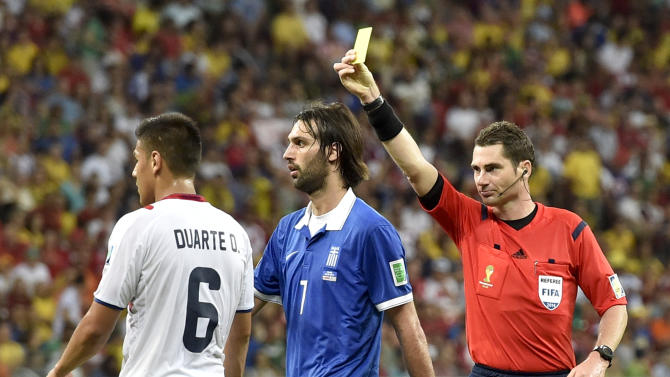 Referee Benjamin Williams, of Australia, right, gives Costa Rica's Oscar Duarte a yellow card during the World Cup round of 16 soccer match between Costa Rica and Greece at the Arena Pernambuco in Recife, Brazil, Sunday, June 29, 2014. (AP Photo/Martin Meissner)