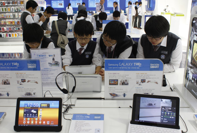 South Korean students use Samsung Electronics&#39; new tablet Galaxy Tab 10.1 at its showroom in Seoul, South Korea, Friday, Sept. 23, 2011. A top Samsung Electronics Co. executive says her company will take a more aggressive stance against its smartphone and tablet rival Apple Inc. in a global patent dispute. (AP Photo/Lee Jin-man)