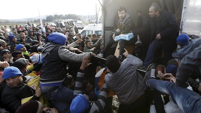 Stranded migrants fight over goods given away by locals at the Greek-Macedonian borders near the Greek village of Idomeni