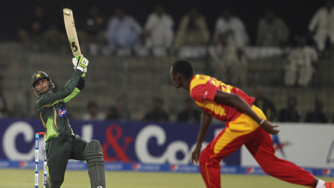 Pakistan's Shoaib Malik hits boundary as Zimbabwe's Christopher Mpofu looks on during a one-day international match at the Gaddafi Stadium in Lahore, Pakistan, Tuesday, May 26, 2015. Malik made an impressive return to limited-overs cricket with a blistering century on Tuesday, propelling Pakistan to 375-3 in the first one-day international against Zimbabwe. (AP Photo/K.M. Chaudary)