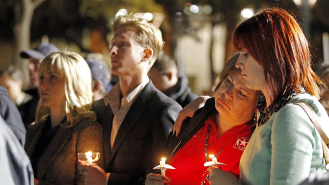 People gather in Centennial Plaza in Midland, Texas on Saturday, Nov. 17, 2012 for a candlelight vigil held in honor of four veterans who were killed when a freight train hit a parade float Thursday. (AP Photo/Midland Reporter-Telegram, James Durbin)