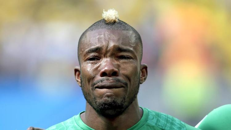 Ivory Coast's Serey Die is overcome with emotion as they play the national anthem before  the group C World Cup soccer match between Colombia and Ivory Coast at the Estadio Nacional in Brasilia, Brazil, Thursday, June 19, 2014