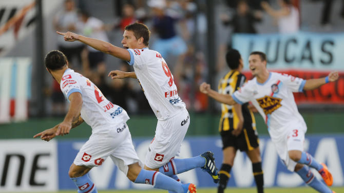 Argentina's Arsenal Julio Furch, center, celebrates after scoring against Uruguay's Penarol during a Copa Libertadores soccer match in Buenos Aires, Argentina, Thursday, March 13, 2014