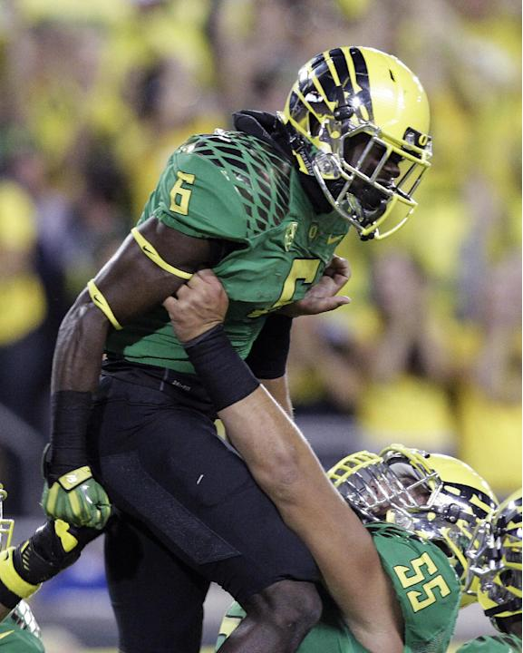 Oregon running back De'Anthony Thomas, left, celebrates his touchdown with offensive lineman Hroniss Grasu during the first half of an NCAA college football game against Washington in Eugene, Ore., Sa