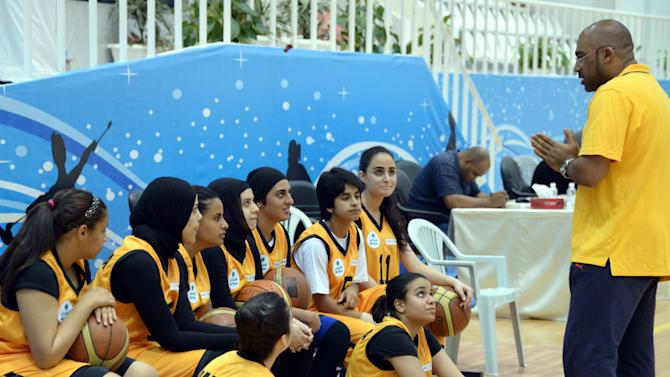 Kuwait's Qadsiya Club women basketball team listen to their coach, during the Women's Games, at Salwa Al Sabah Sports Center in Qurein, Kuwait, Thursday, May 9, 2013. The event is part of a new initiative launching sports leagues for women, including basketball, table tennis and athletic leagues for the first time in Kuwait illustrating how the landscape for women athletes is improving across the Persian Gulf where hard-liners have long opposed women playing sports. (AP Photo/Gustavo Ferrari)