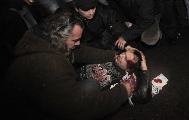 People help wounded protester during a protest against high electricity prices in Sofia,  late Tuesday, Feb. 19, 2013.  Bulgaria's prime minister announced on Tuesday that the license held by a Czech