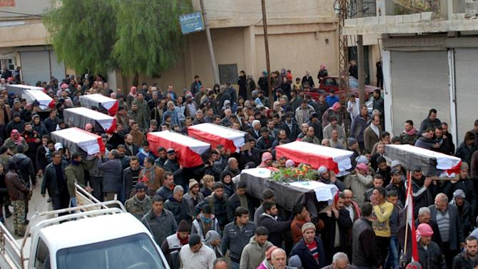 In this photo released by the Syrian official news agency SANA, Syrian citizens carry the coffins wrapped by Syrian flags for the victims who were killed Thursday by a car bomb, during their funeral processions, at al-Kaffat village in the central Hama province, Syria, Friday, Jan. 10, 2014. Rebel-on-rebel fighting between an al-Qaida-linked group and an array of more moderate and ultraconservative Islamists has killed nearly 500 people over the past week in northern Syria, an activist group said Friday, in the most serious bout of violence among opponents of President Bashar Assad since the civil war began. (AP Photo/SANA)