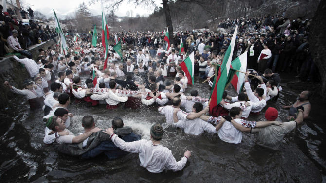Believers sing and dance in the icy waters of river Tundzha as they celebrate Epiphany day in the town of Kalofer, Bulgaria, Sunday, Jan. 6, 2013. Traditionally, an Eastern Orthodox priest throws a cross in the river and it is believed that the one who retrieves it will be healthy through the year. (AP Photo/Valentina Petrova)
