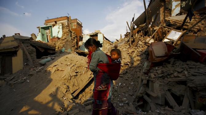 Woman carrying a girl walks along collapsed houses after the April 25 earthquake at Sankhu