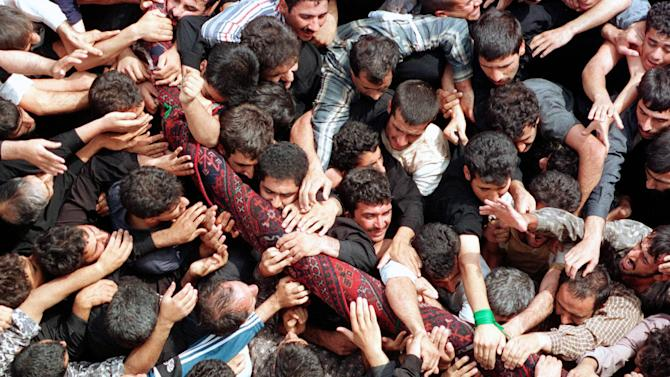 """FILE-- In this Sept. 29, 2000, file photo, Iranian mourners try to touch and carry the sacred rug after it has been """"washed"""" in Ardahal near city of Kashan about 260 kms south of capital of Tehran, Iran. It has been more than 1300 years since the people of the Iranian hamlet of Fin and thousands from areas in the vicinity of the city of Kashan, in the historic central province of Isfahan, first began commemorating the anniversary of the martyrdom of Sultan-Ali son of Imam Mohammad Baqer who is the fifth Imam in the Prophet Mohammad's holy house hold.The commemoration is held annually by on the fourth Friday of September near his mausoleum on the skirts of the Karkas mountain range and a nearby river. The ceremonies are named Rug Washing in the local jargon because the body of the martyred Shiite saint was wrapped up in one before it was buried. The rug woven by the people of Kashan -- well-known for their rug weaving skill-- had been originally given to Sultan-Ali when he was alive to use as a praying rug. The rug used in these ceremonies is a replica of the original. (AP Photo/Hasan Sarbakhshian, File)"""