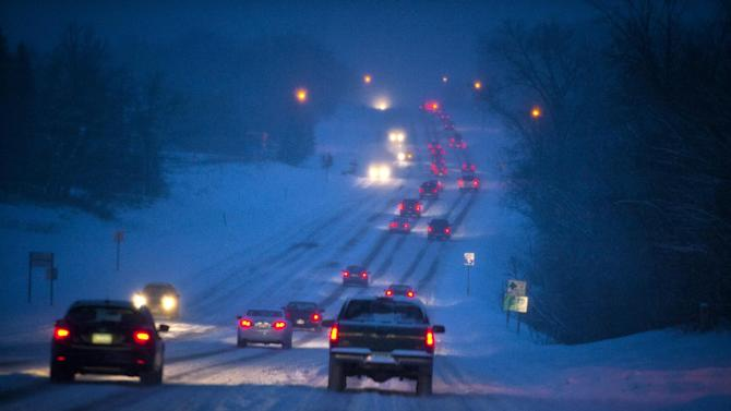Heavy snow, especially toward the south suburbs made for slow traffic along Diffley Road in Eagan, Minn., Friday, Feb. 22, 2013. A major snowstorm that buried parts of the Midwest grazed Minnesota, where two to three inches of snow snarled the morning commute in the Twin Cities area. (AP Photo/The Star Tribune, Glen Stubbe)  MANDATORY CREDIT; ST. PAUL PIONEER PRESS OUT; MAGS OUT; TWIN CITIES