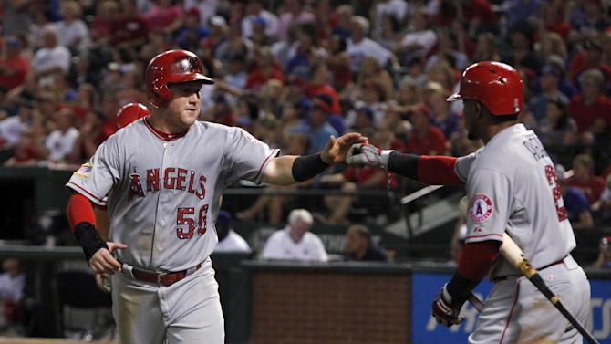 Los Angeles Angels' Kole Calhoun (56) is met at home by Erick Aybar after scoring on a double by Albert Pujols during the sixth inning of a baseball game against the Texas Rangers, in Arlington, Texas, on Saturday, July 4, 2015. (AP Photo/Brad Loper)