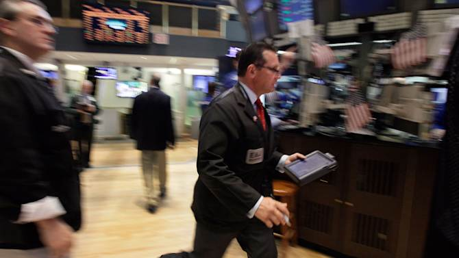 Trader Edward Curran walks briskly across the floor of the New York Stock Exchange Wednesday, June 20, 2012. Stocks edged lower early Wednesday after investors saw signs that economies could be slowing down in both the West and China. (AP Photo/Richard Drew)