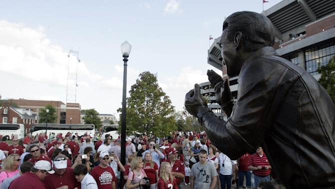 FILE - In this Oct. 8, 2011, file photo, fans gather around the statue of coach Nick Saban outside Bryant Denny Stadium before an NCAA college football game between Alabama and Vanderbilt in Tuscaloosa, Ala. (AP Photo/Butch Dill, File)