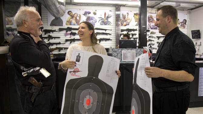 """Rev. """"Jimmy Mac"""" McNamara, also known as the Pistol Packing Preacher, talks with Tanya, center, and Ted Morris, right, after the two took their wedding vows from him and then fired guns on the shooting range at the Guns and Ammo Garage, Thursday, Feb. 14, 2013, in Las Vegas.   The shooting range and gun store offered free vow renewals and wedding ceremonies by McNamara throughout the day on Thursday. (AP Photo/Julie Jacobson)"""