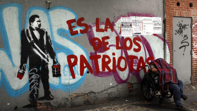 "A man rests next to a graffiti that reads in Spanish, ""Is of the patriots,"" next to a stencil mural of Venezuela's late President Hugo Chavez in downtown Caracas, Venezuela, Thursday, March 14, 2013. Venezuela's acting president said Wednesday that it is highly unlikely Hugo Chavez will be embalmed for permanent viewing because the decision to do so was made too late and the socialist leader's body was not properly prepared on time. Chavez died on March 5. The decision to preserve his body permanently was announced two days later. (AP Photo/Rodrigo Abd)"