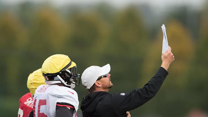 Atlanta Falcons players check a play during a training session at the Arsenal FC training ground in London Colney, England, Wednesday Oct. 22, 2014. The Falcons will play the Detroit Lions in an NFL football game at London's Wembley Stadium on Sunday, Oct. 26