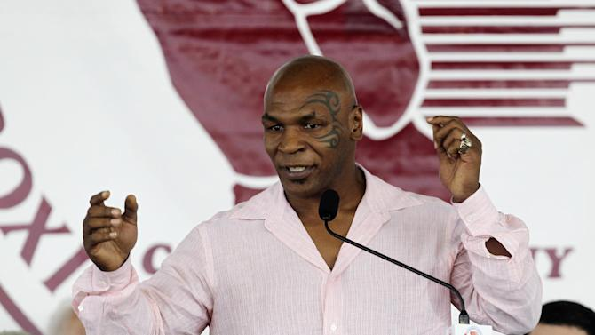 "FILE - This June 12, 2011 file photo shows former boxer Mike Tyson at the Boxing Hall of Fame in Canastota, N.Y.  Tyson announced Monday, June 18, 2012 that he will team up with director Spike Lee to bring his one-man show ""Mike Tyson: Undisputed Truth""  to the Longacre Theatre in New York for six nights only, from July 31 to Aug. 5.  The show, a raw confessional on the highs and lows of the life of the retired heavyweight and tabloid target, made its debut in April at the MGM Grand in Las Vegas. It will mark Lee's debut as a Broadway director. (AP Photo/Mike Groll)"