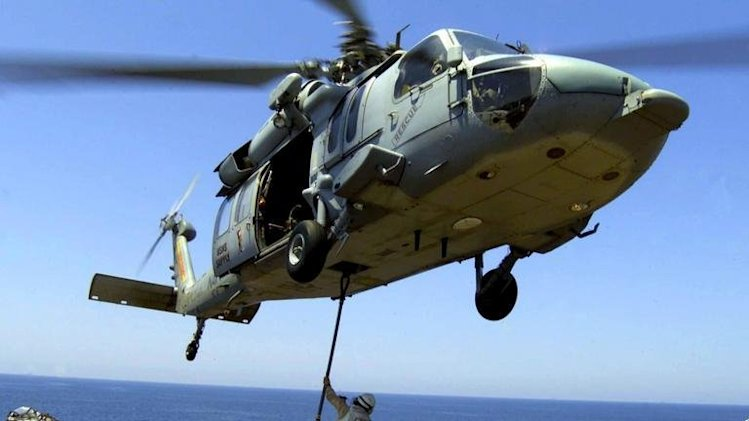 This US Navy photo received 26 March 2004, shows a US Marine aboard USS Wasp and an MH-60S Knighthawk helicopter