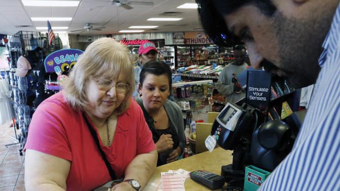 Elizabeth Dillard, left, of Oklahoma City, shows store clerk Mobi, right, the numbers she wants in the Powerball Lottery as she purchases tickets in Oklahoma City, Friday, May 17, 2013. Looking on at center is Lindsay Horn. (AP Photo/Sue Ogrocki)