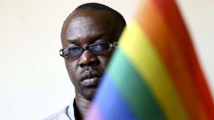 Geoffrey Ogwaro, a gay Ugandan, is seen next to a rainbow flag at his office in the capital Kampala