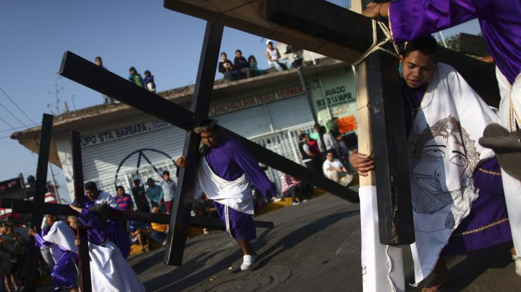 Penitents carry crosses during re-enactment of crucifixion of Jesus Christ on Good Friday in Iztapalapa in Mexico City