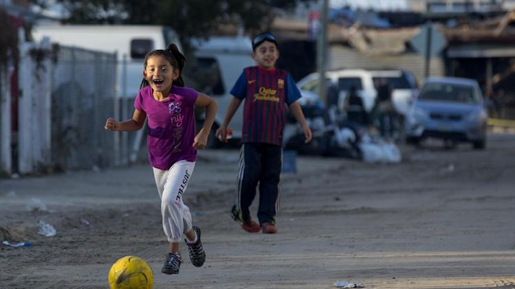 Nicoll Cortez, 6, gleefully chases a soccer ball as she plays with her brother Anthony Lopez, 7, on their sand and debris covered street in the Rockaway Park neighborhood of the borough of Queens, New York, Sunday, Nov.11, 2012, in the wake of Superstorm Sandy. (AP Photo/Craig Ruttle)